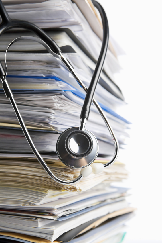 Medical record concept using stethoscope in front of pile of paper. Selective focus